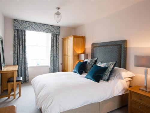 Luxury style double bedroom. Beautiful, plush cushions scattered on the bed, with light shining through the dressed window.