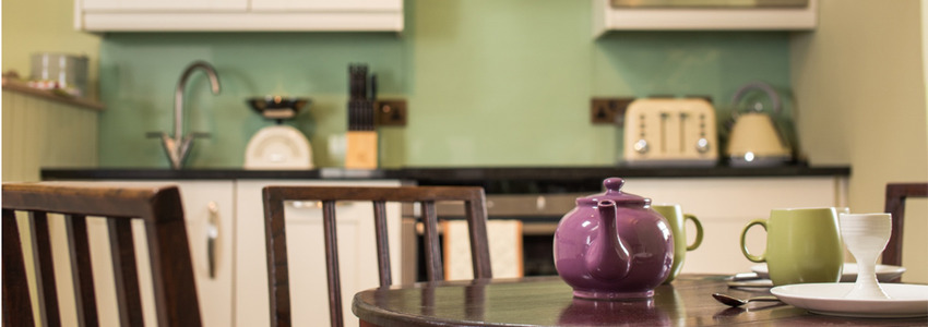 Traditional kitchen table in a cosy style kitchen with a purple tea pot sitting on the table