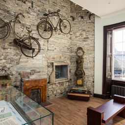 Inside an exhibition at Cardigan castle, display cases and chairs hanging on walls.